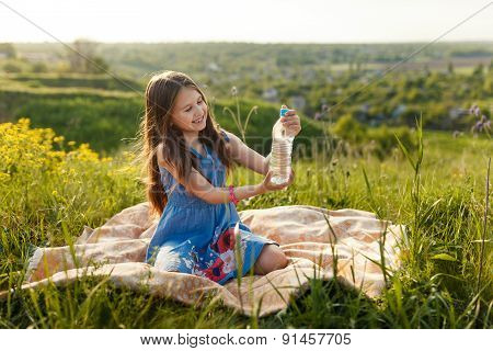 Girl In Grass With Plastic Water Bottle