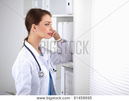 Woman doctor is standing near window .