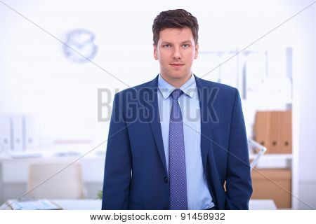 Business man or manager standing against his desk at the office .