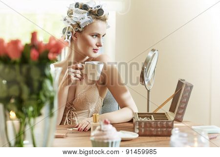 Beautiful young blonde lady drinking coffee at the morning