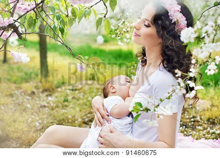 Young mother feeding her little baby in a spring orchard