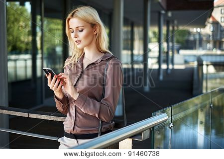 Young blonde lady with a smartphone