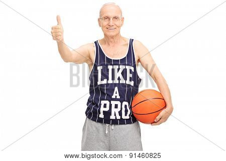Studio shot of a cheerful senior holding a basketball and giving a thumb up isolated on white background