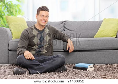 Young relaxed man sitting on the floor at home in front of a modern gray couch and looking at the camera