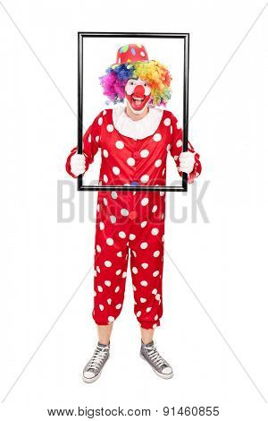 Full length portrait of a male clown holding a big picture frame and posing behind it isolated on white background