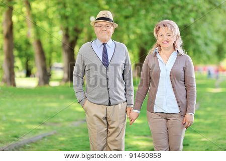 Mature couple holding hands and posing in a park on a sunny summer day