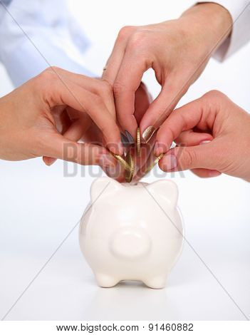 Putting coin into the piggy bank, isolated o white background