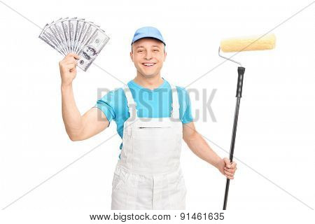 Cheerful young decorator holding a paint roller and a stack of money isolated on white background