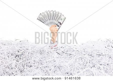 Studio shot of a hand of a man stuck in a pile of shredded paper holding a stack of money above the surface isolated on white background