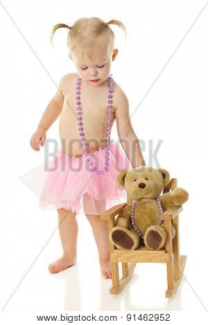 An adorable toddler wearing a necklace and tutu rocking her toy bear who wears a similar necklace.  On a white background.