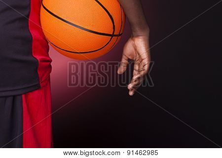 Rear view of a basketball player holding a basketball against dark background