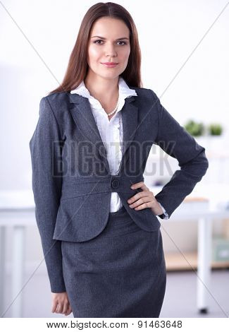 Portrait of businesswoman standing in office .