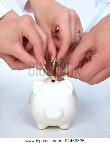 Putting coin into the piggy bank, isolated.