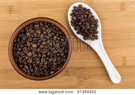 Ceramic Bowl With Coffee Beans And White Spoon On Table