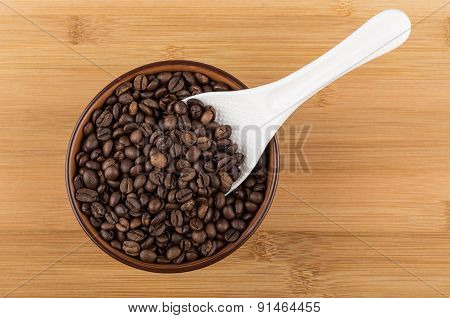 White Plastic Spoon In Brown Ceramic Bowl With Coffee Beans
