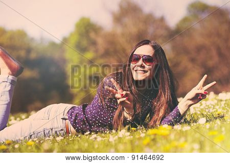 Retro toned portrait of joyful young woman in sunglasses relaxing on green grass and showing victory sign in sunny summer day