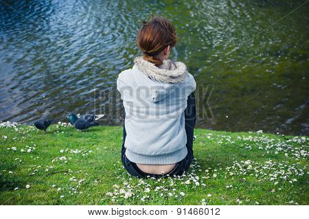 Young Woman Resting By Water In Park