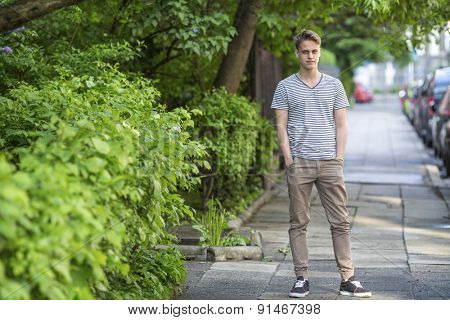 Tall guy standing on the street, a portrait in full growth.