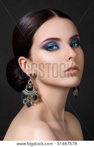 Portrait Of Beautiful Brunet Woman With Blue Earrings