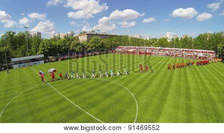RUSSIA, BOGORODSKOE - MAY 14, 2014: Teams walk by soccer field with country flags during international competition at Spartakovec stadium named by N.P. Starostin. Aerial view