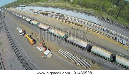 RUSSIA, MOSCOW - APR 30, 2014: Workers unload sleepers from trucks with cranes on building site of railroad beltway widening for opening of passenger traffic. Aerial view