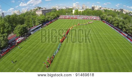 RUSSIA, BOGORODSKOE - MAY 14, 2014: Formation of football teams with country flags during international competition on field at Spartakovec stadium named by N.P. Starostin. Aerial view