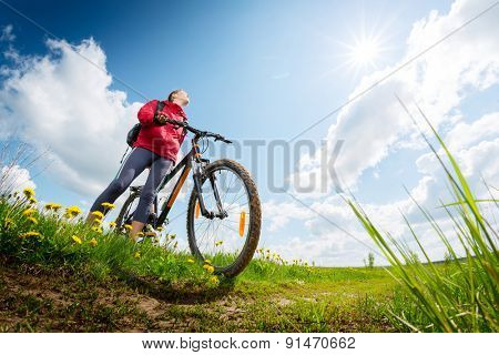 Young lady hiker with bicycle standing on a green summer meadow