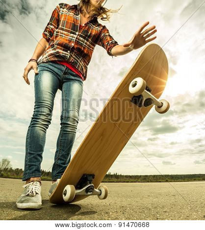 Young lady standing with skateboard