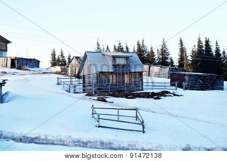 Wooden buildings over snow and sky in wintertime