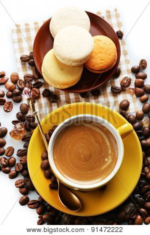Gentle colorful macaroons and black coffee in mug on white background, top view