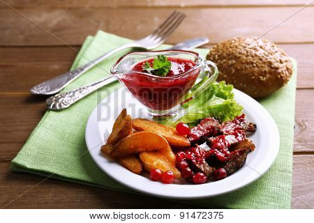 Beef with cranberry sauce, roasted potato slices on plate, on wooden background