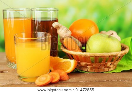 Assortment of healthy fresh juices on wooden table, on bright background