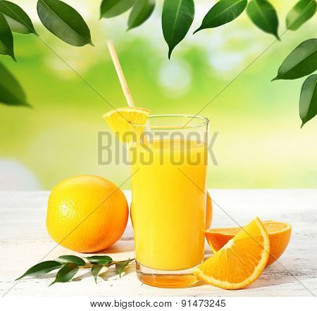 Glass of orange juice and oranges on wooden table and natural background