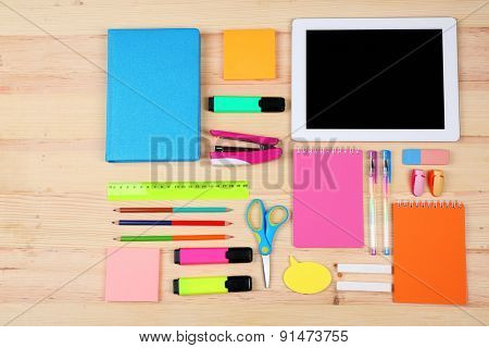 Digital tablet with stationery on wooden background