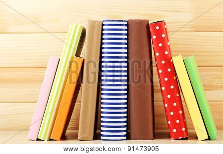 Books on shelf, close-up, on wooden background