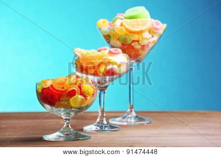 Colorful candies in glasses on table on blue background