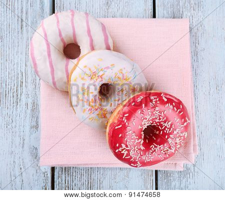 Delicious donuts with icing on napkin on wooden background