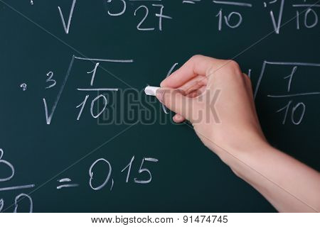Female hand writing formulas on blackboard with chalk close up