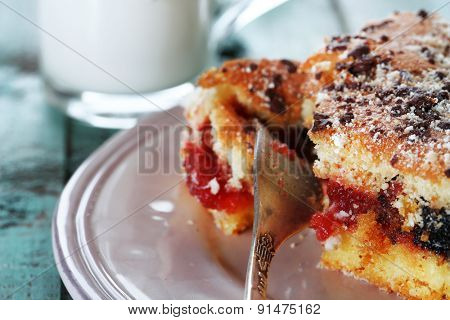 Homemade pie with jam, chocolate and glass of milk on color wooden table background