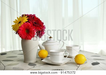 Colorful gerbera in vase with teapot, cups and lemons on table on curtains background