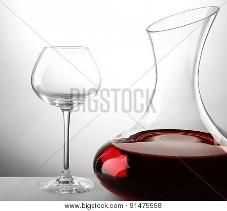 Glass carafe of wine on light background