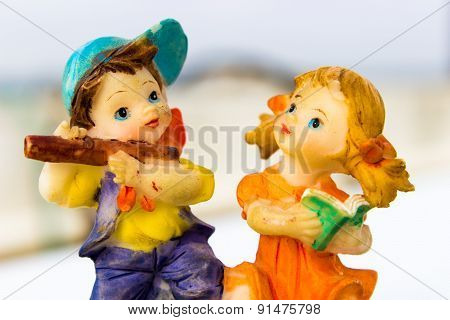 macro photography depicting small statue of a boy playing flute and a girl singing