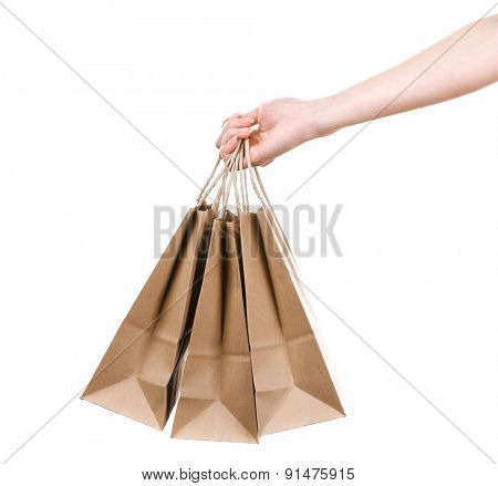Female hand holding paper shopping bag isolated on white