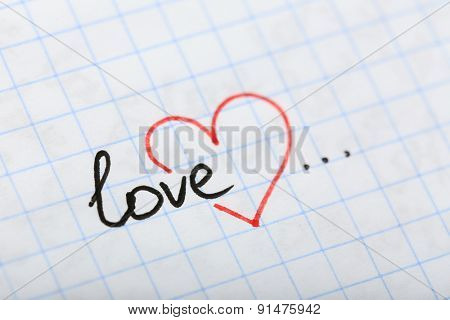 Word LOVE with heart written on sheet of paper background