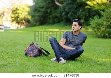Handsome brunet young man in casual clothing sitting in the park