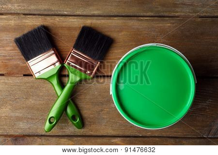 Paint can and paint brushes on wooden background