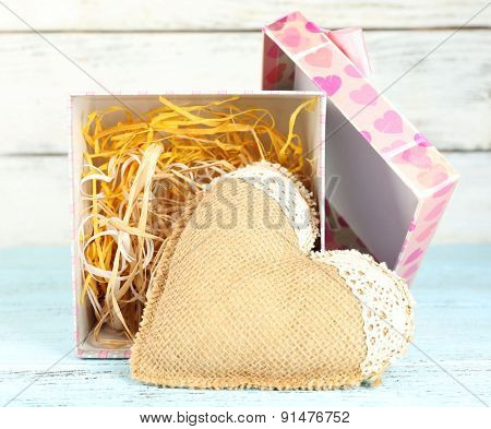 Vintage heart in present box on wooden table