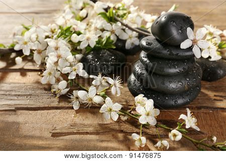Spa stones with spring flowers on wooden background