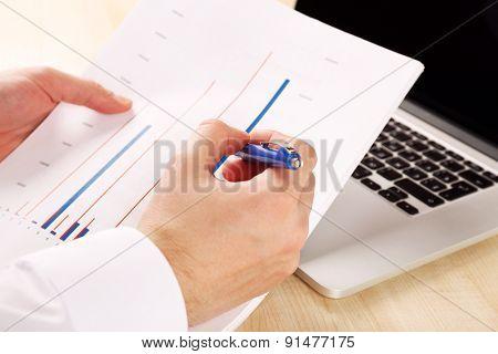Businessman analyzing charts, closeup