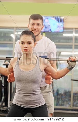 Young fitness coach stands by the girl drill